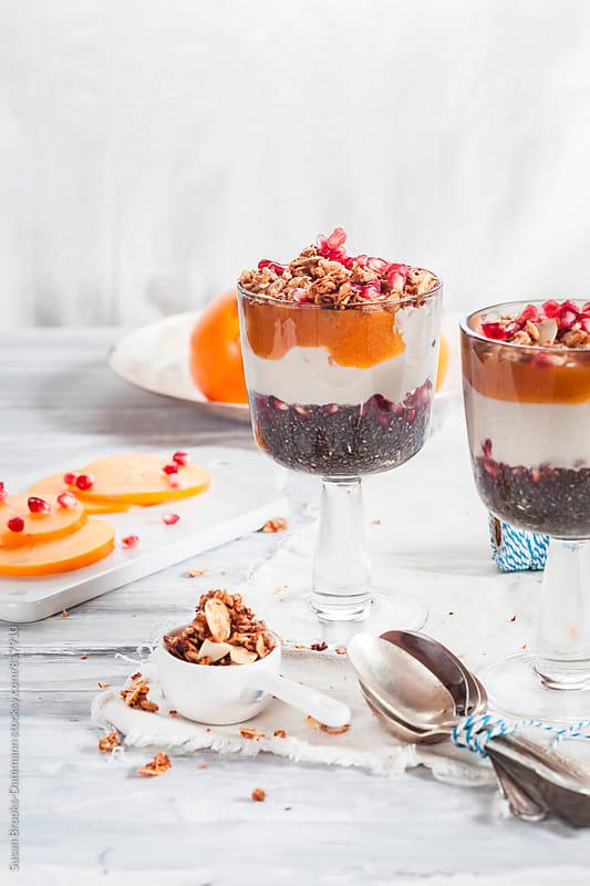 Yogurt with kaki-fruit and pomegranate seeds by Susan Brooks-Dammann for Stocksy United