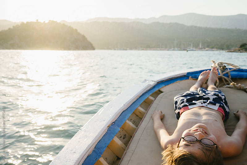 Boy lying down on small boat while sun sets.  by Kirstin Mckee for Stocksy United
