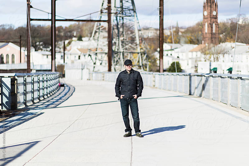 Man standing on bridge in bright sun by Holly Clark for Stocksy United