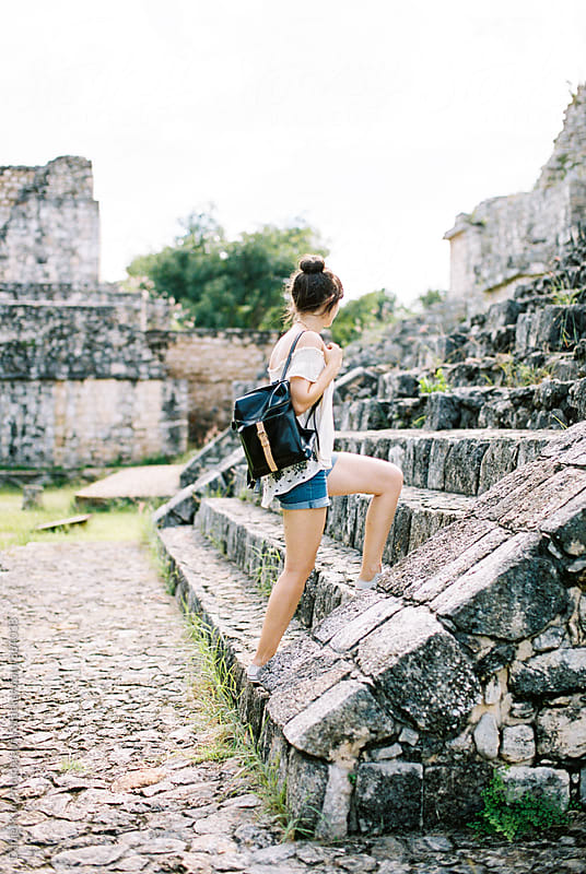 Woman walking up mayan ruin steps by Daniel Kim Photography for Stocksy United