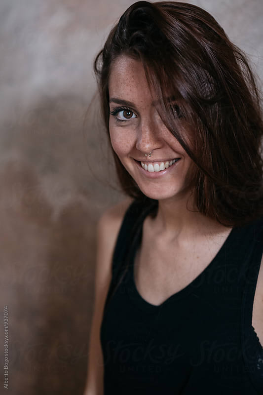 Smiling woman with freckles looking at camera by Alberto Bogo for Stocksy United