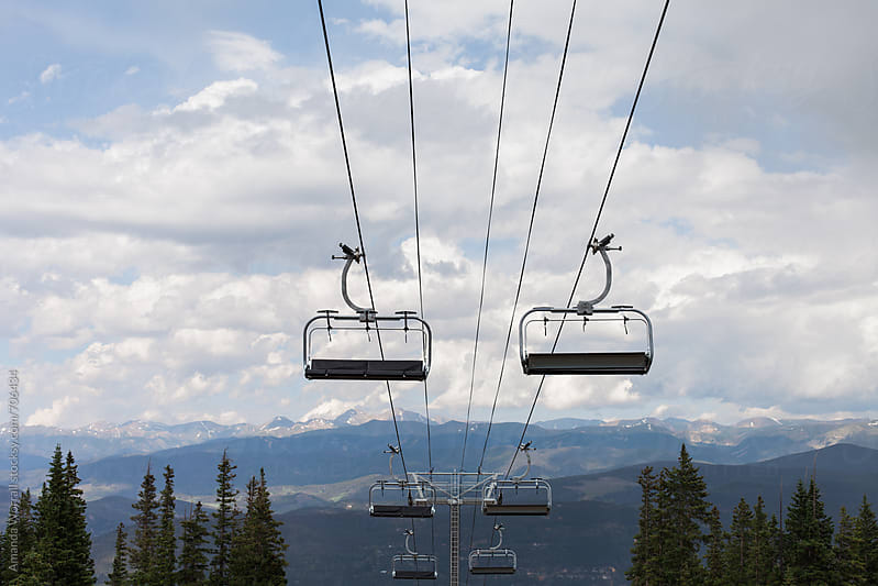 Perspective of chair lifts at a ski resort in the summer by Amanda Worrall for Stocksy United