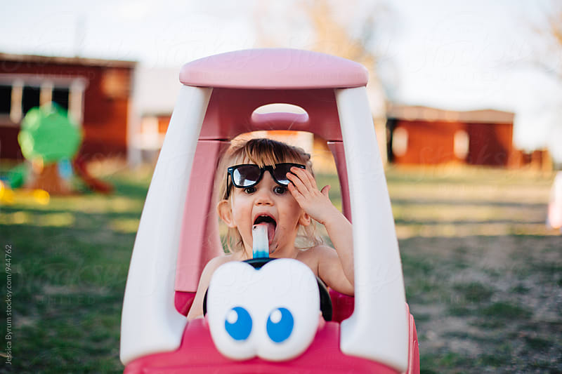 Toddler girl eating popsicle in pink toy car by Jessica Byrum for Stocksy United