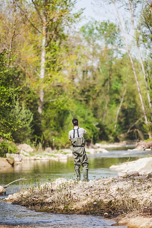 Young Man Fishing on the Bank of a Small River by Giorgio Magini for Stocksy United