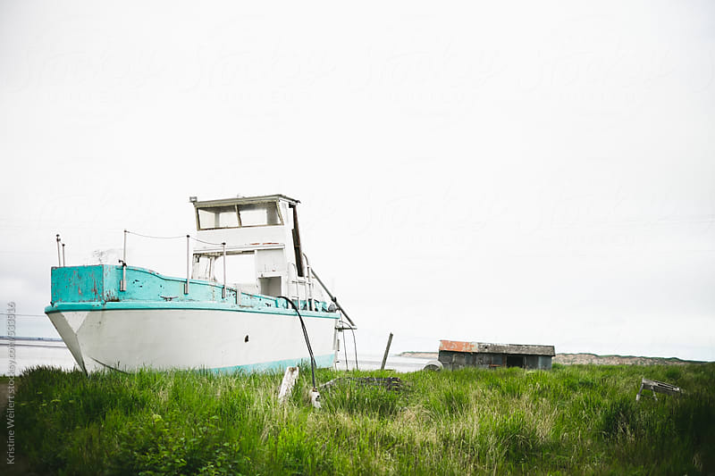 Beautiful blue and white fishing boat washed up on land by Kristine Weilert for Stocksy United