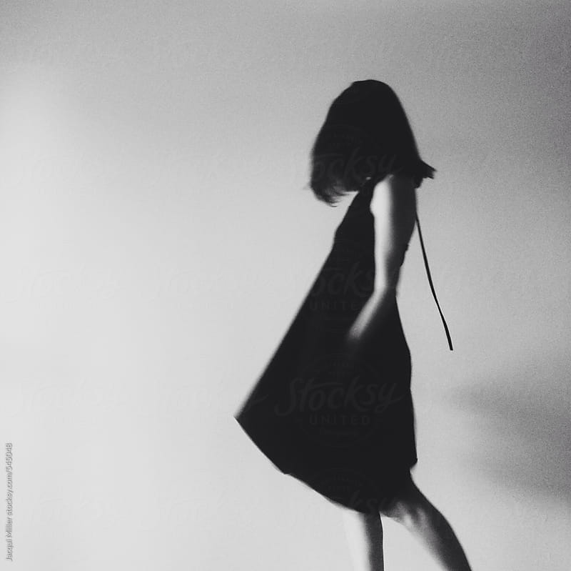 Black and White minimalist image of unrecognisable woman wearing a dress by Jacqui Miller for Stocksy United