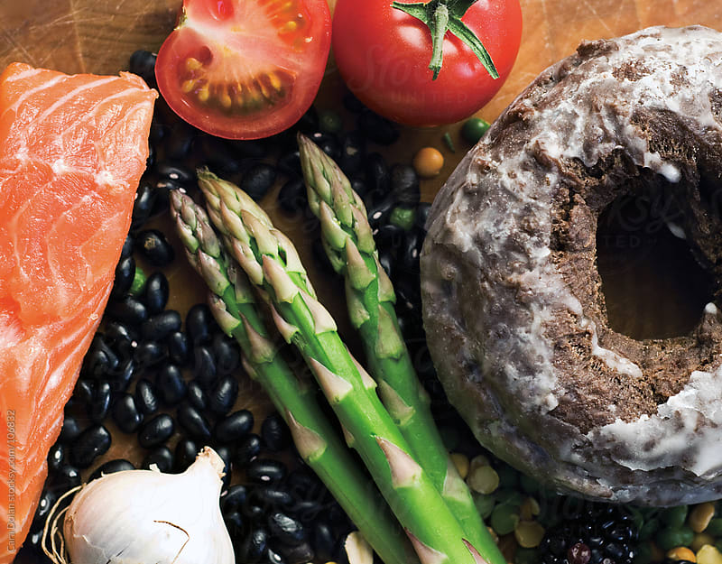 A variety of healthy, wholesome foods with a chocolate glazed doughnut by Cara Dolan for Stocksy United