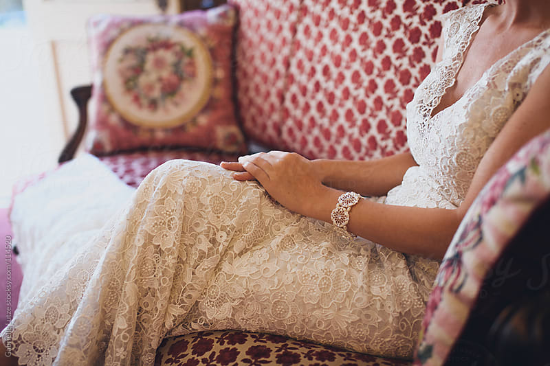Bride sitting on a Victorian Couch by Gabrielle Lutze for Stocksy United