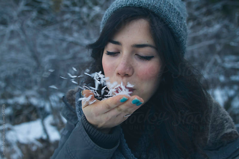 Girl blows snow out of hand by Jesse Morrow for Stocksy United