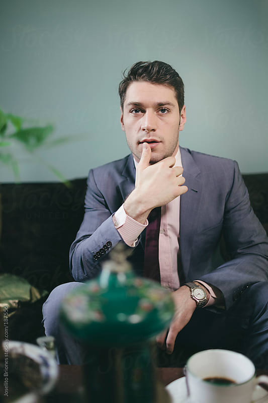 Stylish Man in Suit Touching Lips by Joselito Briones for Stocksy United