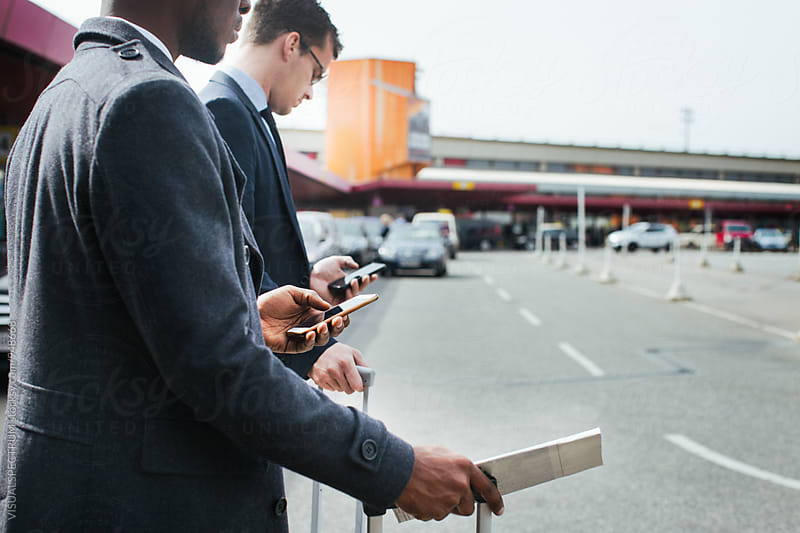 Black and Caucasian Businessmen Using Their Cellphones as They Wait For Taxi by Julien L. Balmer for Stocksy United