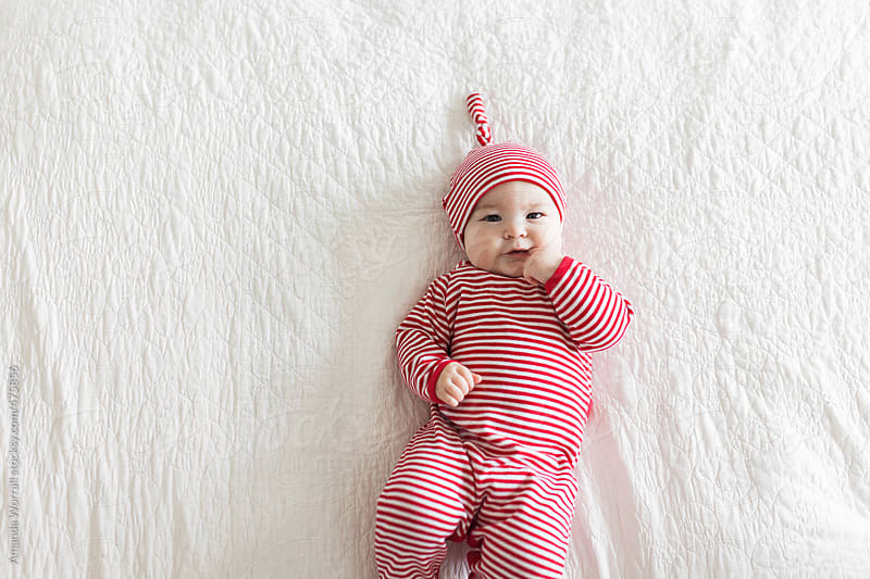 Baby wearing red and white striped Christmas cap and pajamas by Amanda Worrall for Stocksy United
