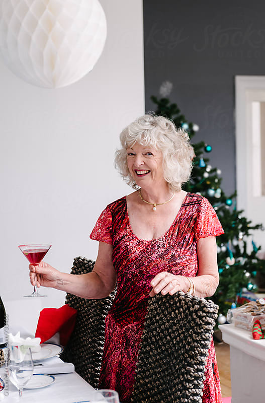 senior woman enjoying a red cocktail at christmas time by Gillian Vann for Stocksy United