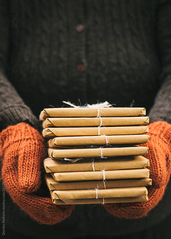 Mittened hands holding a stack of brown paper packages by Deirdre Malfatto for Stocksy United
