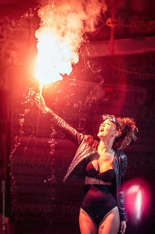 happy fashionable young girl holding a red torch by Igor Madjinca for Stocksy United