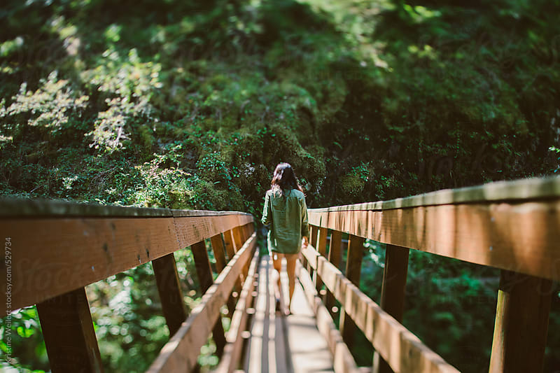 Woman surrounded by beautiful forest walking across a wooden bridge by Kristine Weilert for Stocksy United