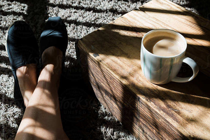 Woman with a coffee, relaxing in harsh light on floor with feet crossed by Jacqui Miller for Stocksy United