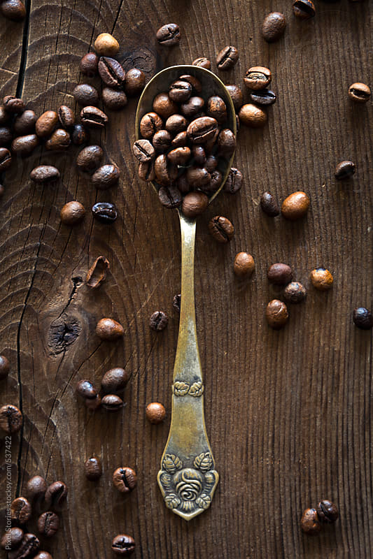 Roasted coffee beans on vintage spoon by Pixel Stories for Stocksy United