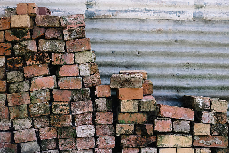 Old bricks piled against shed by Rowena Naylor for Stocksy United