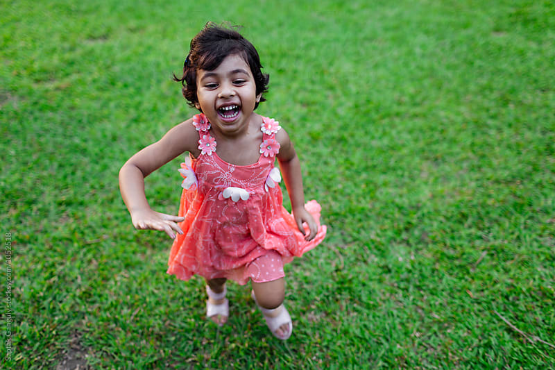 Cute little girl running on a green field by Saptak Ganguly for Stocksy United