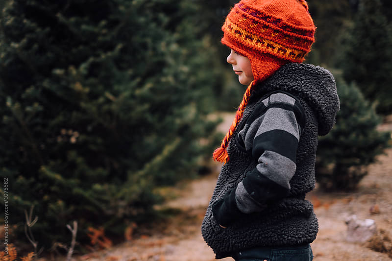 child with orange (or red) hat at a christmas tree farm by Léa Jones for Stocksy United