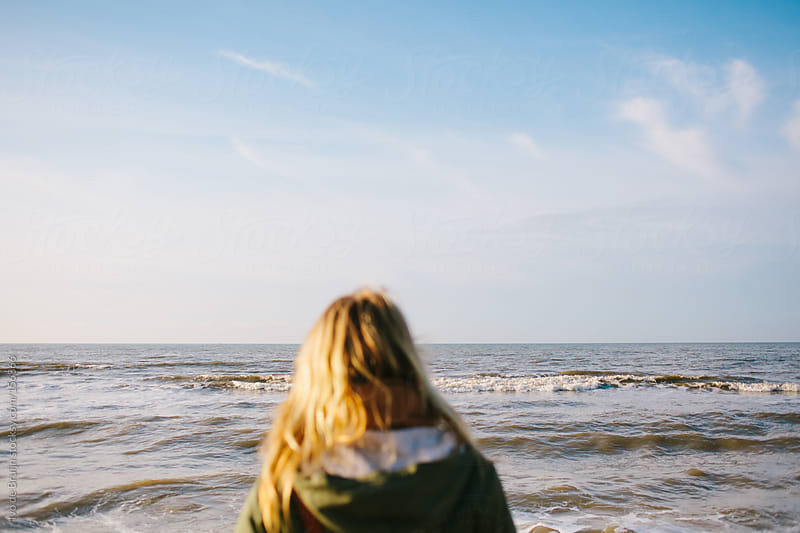 Photo of a young blond woman looking at the tranquil ocean by Ivo de Bruijn for Stocksy United
