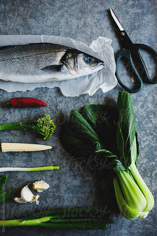 Sea bass and ingredients for cooking. by Darren Muir for Stocksy United
