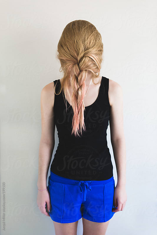 Teen girl hides behind hair that she has plaited in front of her face by Jacqui Miller for Stocksy United