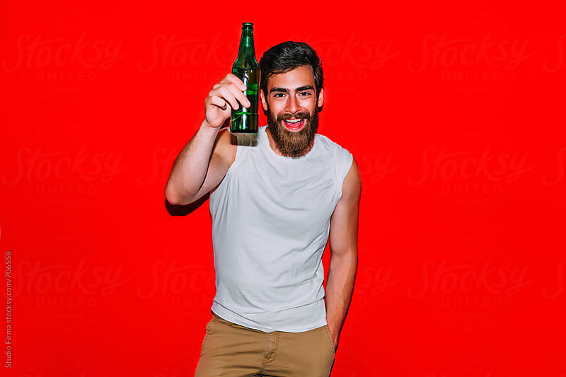 Man with beer bottle smiling. by Studio Firma for Stocksy United