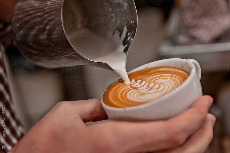 barista pouring milk into coffee to create a rosetta, or latte art. by Gillian Vann for Stocksy United