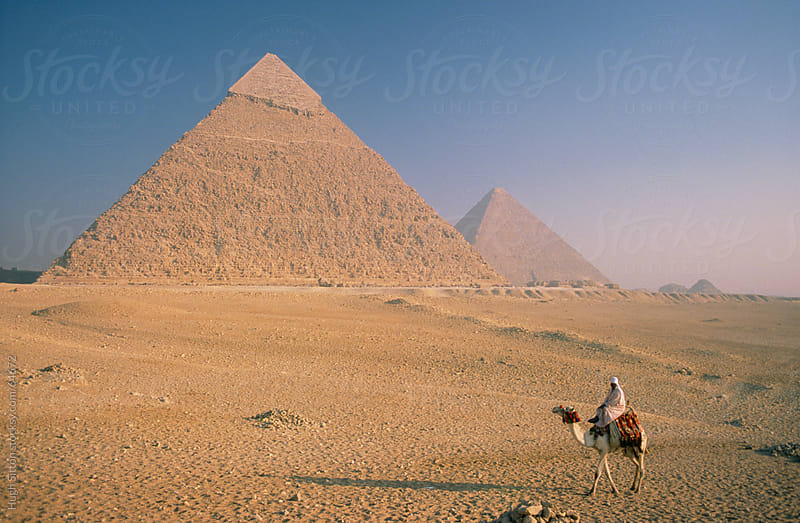 Arab riding camel past the Pyramids of Egypt. by Hugh Sitton for Stocksy United