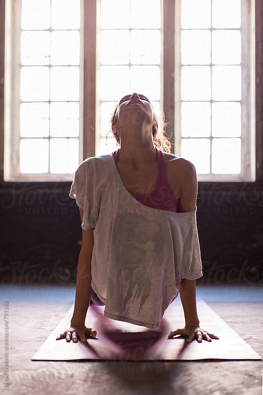 Young woman practicing in a yoga studio. Upward facing dog during sun salutations. by Jovo Jovanovic for Stocksy United