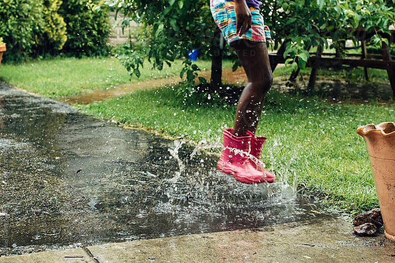 Black girl jumping in rain puddle by Gabriel (Gabi) Bucataru for Stocksy United