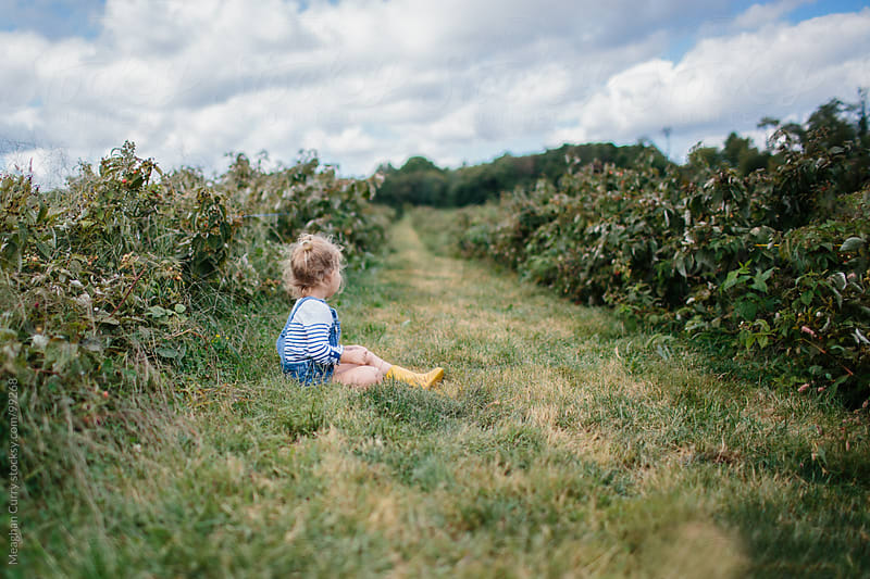 little girl taking a break from picking raspberries in overalls and boots by Meaghan Curry for Stocksy United