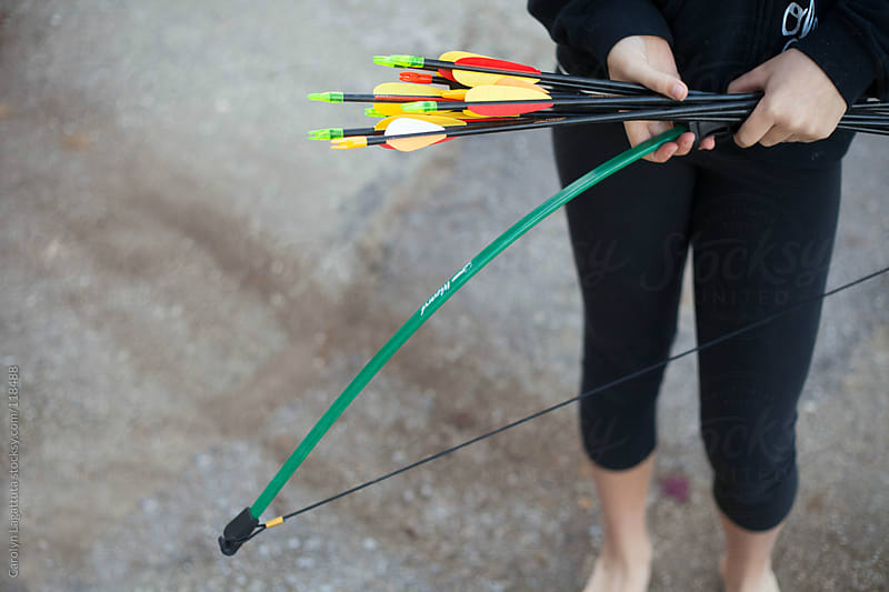 Girl holding her bow and arrows - ready to shoot by Carolyn Lagattuta for Stocksy United