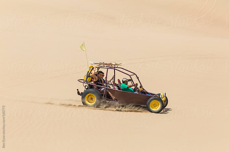 Dune buggy with passengers speeding across open ground by Ben Ryan for Stocksy United
