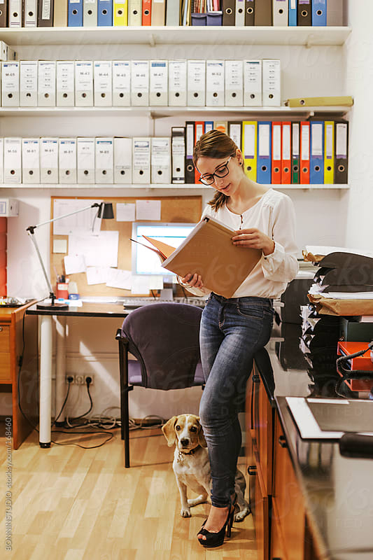 Businesswoman working at office with her dog. by BONNINSTUDIO for Stocksy United