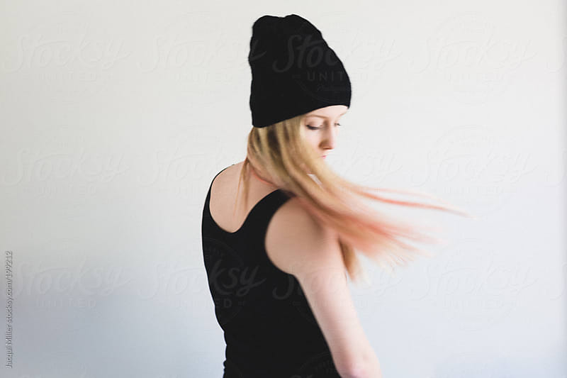 Movement shot of teen girl, wearing a black beanie, flicking her long blonde and pink hair by Jacqui Miller for Stocksy United