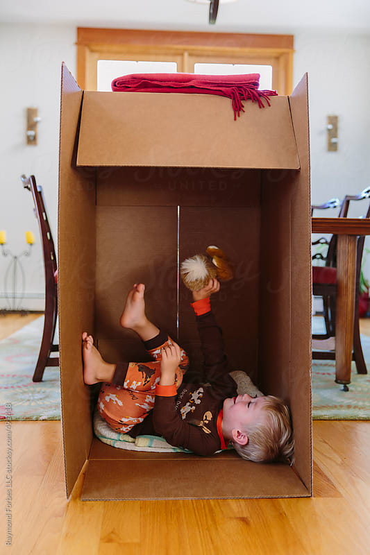 Boy Playing in Box at Home by Raymond Forbes LLC for Stocksy United