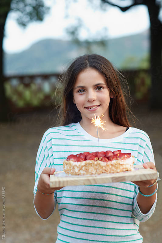Cute young girl carrying a birthday cake by Miquel Llonch for Stocksy United