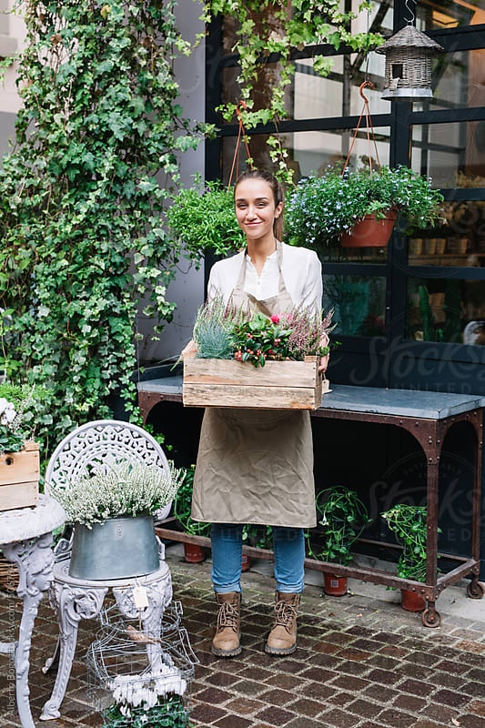 Florist standing in front of the flower shop by Alberto Bogo for Stocksy United