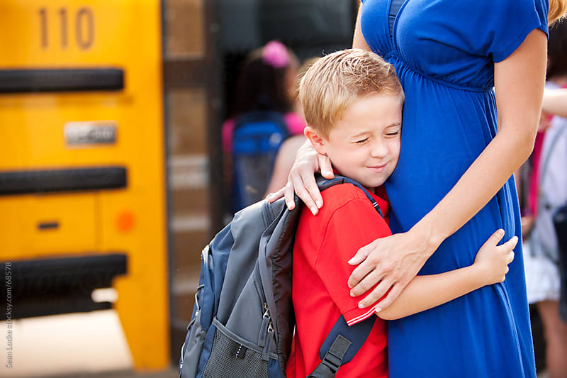 School Bus: Boy Sad to Leave Mother for School by Sean Locke for Stocksy United