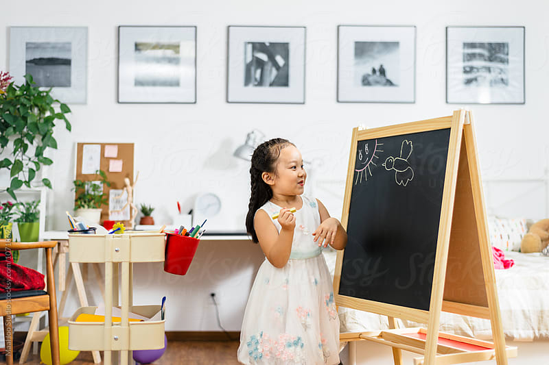 Cute little girl drawing at home using an easel stand by MaaHoo Studio for Stocksy United