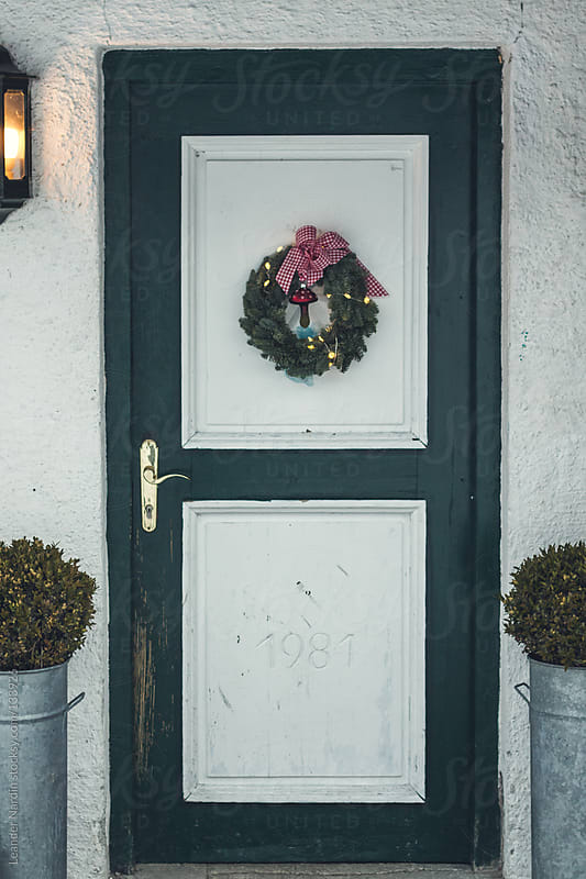 old wooden entrance door christmassy decorated by Leander Nardin for Stocksy United