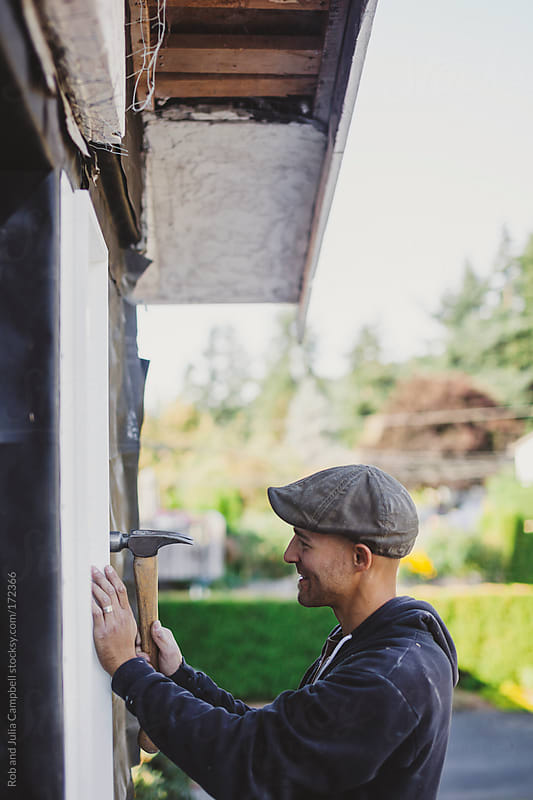 Happy carpenter hammering wall during renovation by Rob and Julia Campbell for Stocksy United
