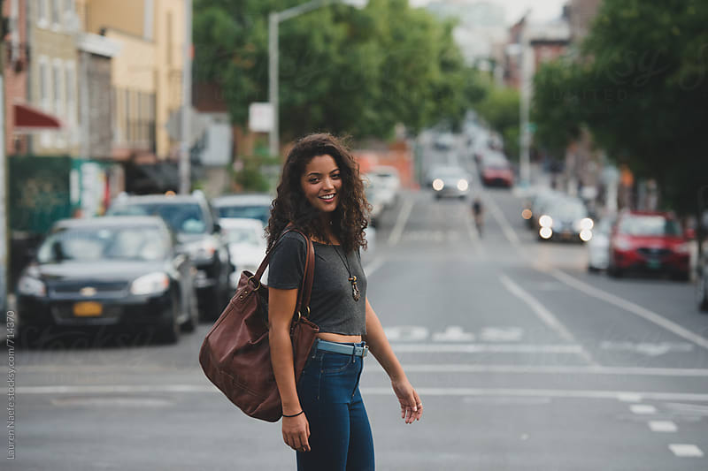 Young woman crossing the street, smiling by Lauren Naefe for Stocksy United