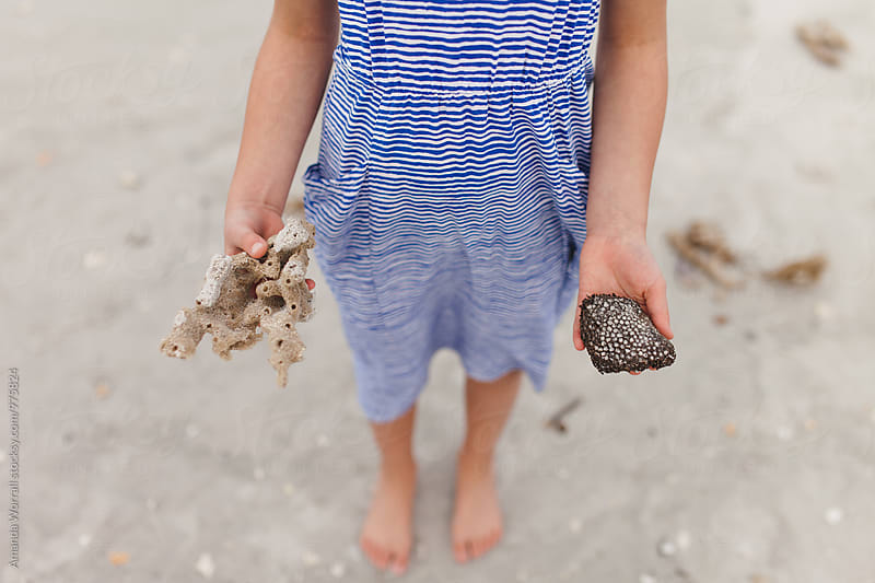 Anonymous girl holding out her treasures found on the beach by Amanda Worrall for Stocksy United