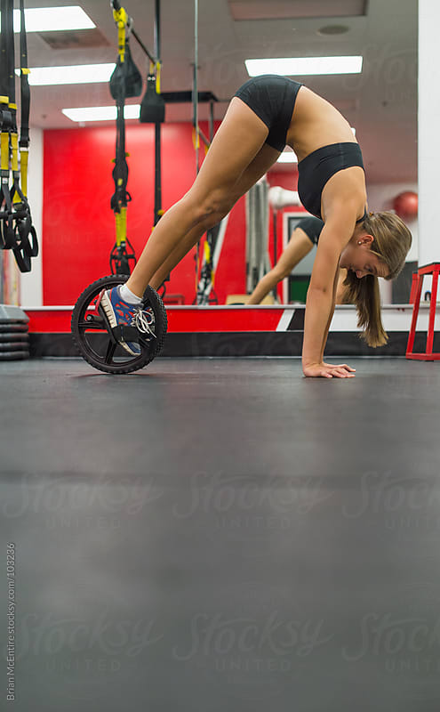 Highly Fit Woman Athlete Doing Pike Push-ups In Gym with Ab Wheel by Brian McEntire for Stocksy United
