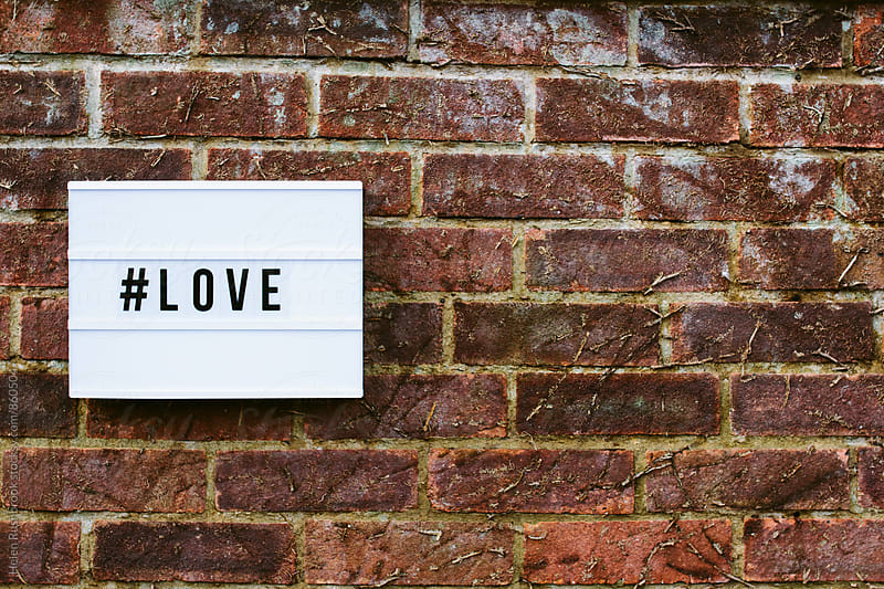 #love spelled out on a cinematic light box on an old brick wall by Helen Rushbrook for Stocksy United