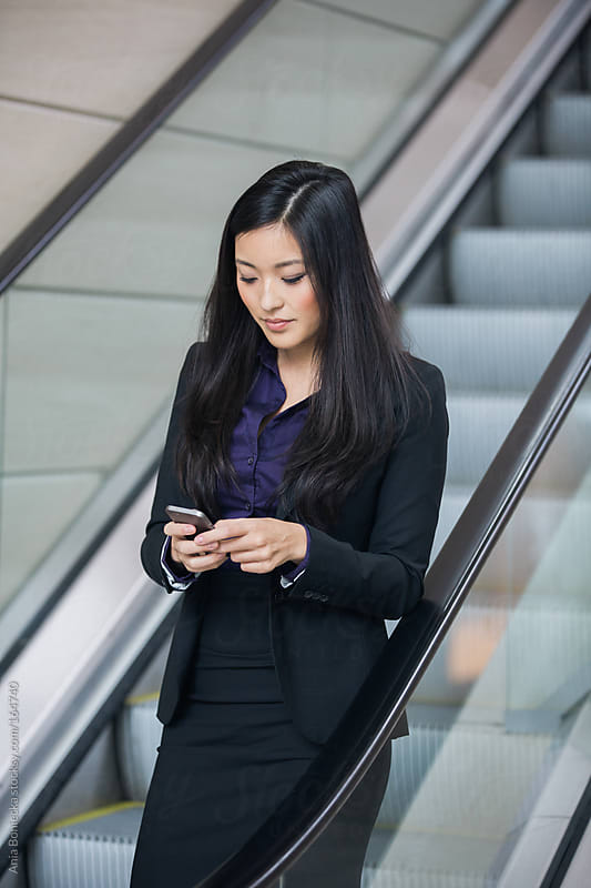 Asian businesswoman checking her cellphone while waiting on an escalator by Ania Boniecka for Stocksy United
